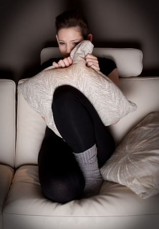 A scared young woman watching a horror movie at home  photo