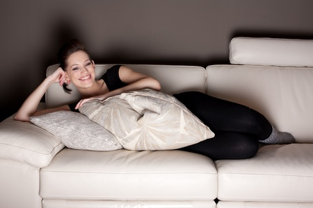 A beautiful young woman watching TV, lying on the couch comfortably  photo