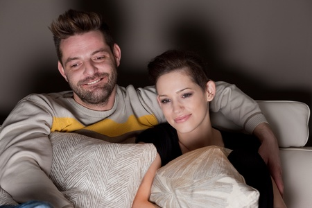 A young couple in love watching TV at home  photo