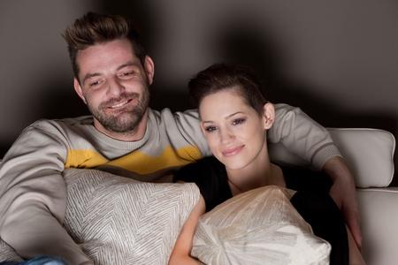 pareja viendo tv: Una joven pareja de enamorados en casa viendo la televisi�n