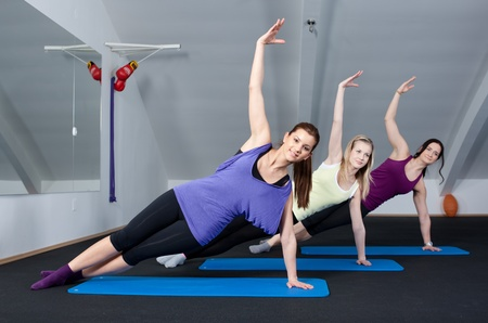 Group of three young women doing exercises in a fitness club  photo