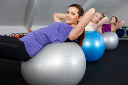 A group of attractive young women doing sit ups at a fitness club Stock Photo - 9689145