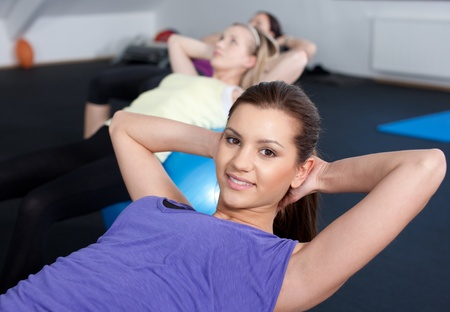 ups: Beautiful and fit young women doing push ups on balls at a fitness club  Stock Photo