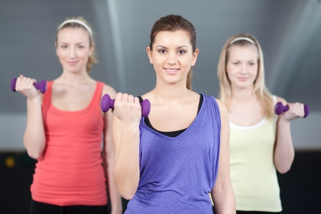 Fit young women doing a biceps exercise with dumbells Stock Photo - 9689128