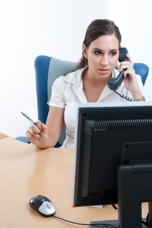 Worried young businesswoman sitting behind the desk, talking on the phone  Stock Photo - 9689312