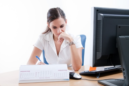 Young beautiful business lady behind the desk planning her business meetings. Stock Photo - 9688719