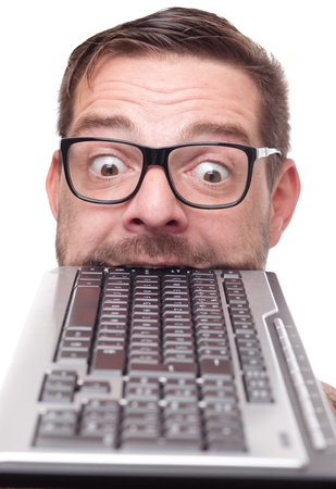 silly face: Eccentric nerd with keyboard in his mouth Stock Photo