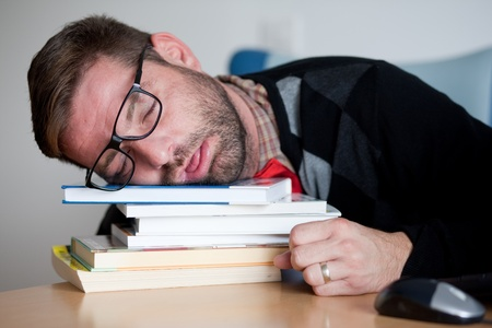 A tired geek sleeping on a bunch of books  Stock Photo