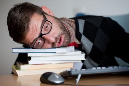A tired nerd falling asleep on a bunch of books