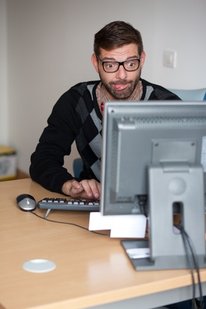 Excited nerd using the computer Stock Photo - 9689287