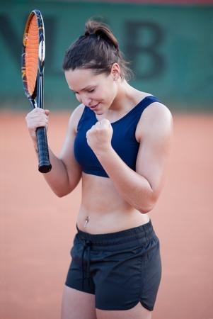 sudoroso: Ganador. Joven mujer celebrando la victoria en un partido de tenis