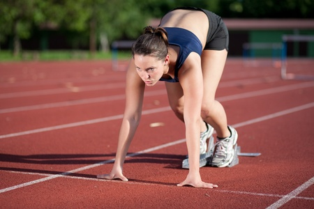 focused: Female athlete getting ready to blast off  Stock Photo