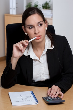 Attractive pensive young businesswoman making calculations and business plans  photo