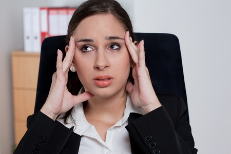 fatigued: Stressed businesswoman having a headache and massaging her head  Stock Photo