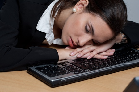 Tired businesswoman sleeping at her desk in her office Stock Photo - 9689053