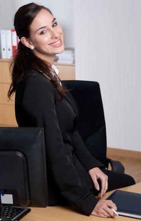 Attractive cheerful young businesswoman, sitting on her desk  photo