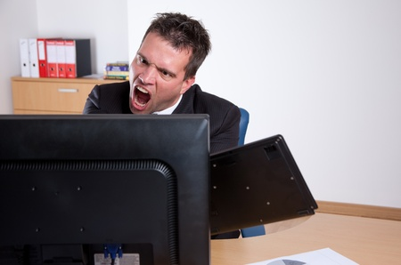 banging: Office rage series. Businessman slamming keyboard on computer monitor.  Stock Photo