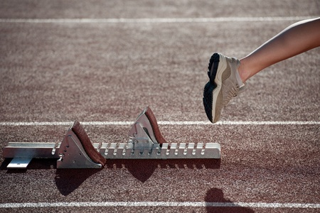 flexed: Athlete leaving the starting blocks for a sprint run on a track  Stock Photo