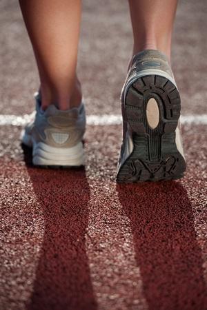 pista de atletismo: Caminando sobre una pista de atletismo. Cerca de zapatillas de ejecuci�n