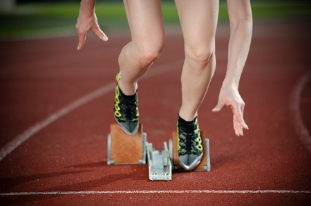 Close-up image of a female runner leaving the starting blocks for a sprint run on a track  photo