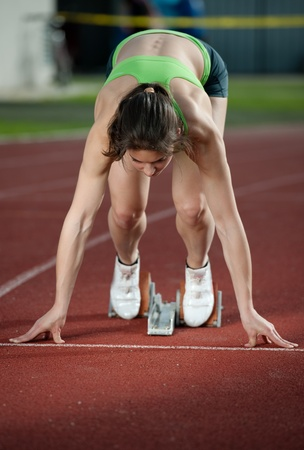 Muscular female sprinter ready to go  photo