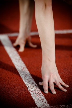 tenseness: Female athletes arms on the starting line. High contrast.