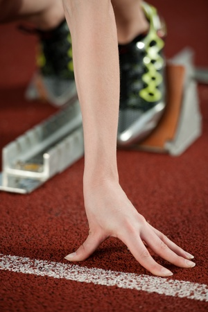 tenseness: Detailed view of a female sprinter ready to go