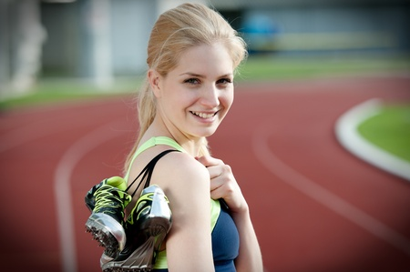 Portrait of a beautiful young female sprinter standing on a running track and holding her sprinting shoes with spikes photo