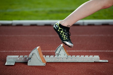 spikes: Female sprinter leaving the starting blocks for a sprint run on a track