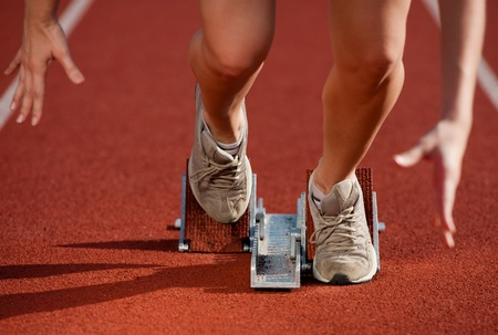 caucasian race: Action packed close-up image of a female athlete leaving the starting blocks for a sprint run on a track  Stock Photo