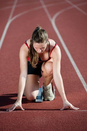 18 20: Young female athlete on a running track, getting ready to go from starting blocks  Stock Photo
