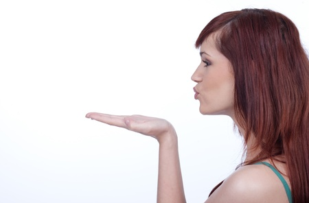 blow: Vista di profilo di una giovane donna che soffia un bacio su sfondo bianco