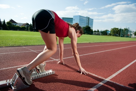 Female athlete in the starting blocks, ready to go  photo