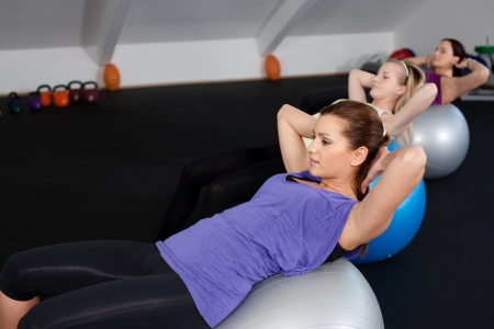 A group of cute girls doing sit ups at a fitness club Stock Photo - 9752812