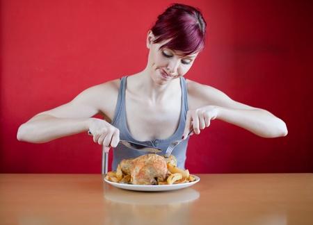 beenderige: Enthousiaste magere jonge vrouw op het punt om een hele kip te eten Stockfoto