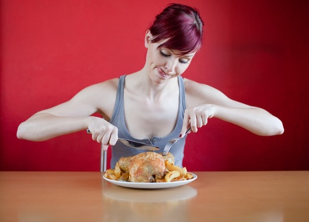 bony: Enthusiastic skinny young woman about to eat a whole chicken