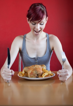 skinny woman: Skinny woman enthusiastically looking at whole chicken on her plate