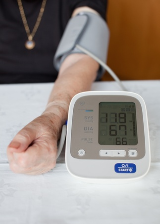 systolic: Senior woman measuring her blood pressure. At home.  Stock Photo