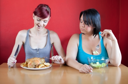 fat person: Tailored diet. Skinny woman is happy because she can eat huge meals, while the overweight woman is looking sadly at her because she has to eat just a few leaves of lattuce.