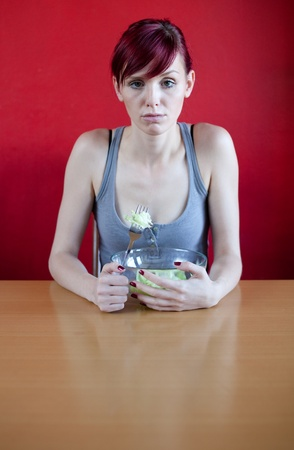 skinny woman: Unhappy skinny woman with her meal, a bowl with a few leaves of lattuce in it. Diet concept. Stock Photo