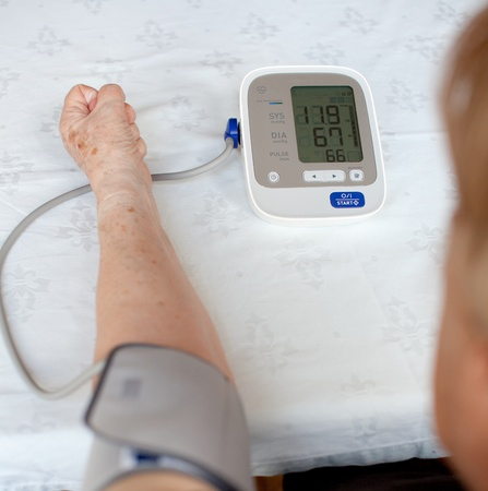 Senior woman measuring her blood pressure. At home. photo