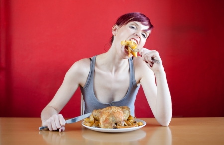 Skinny woman with a whole chicken on her plate stuffing herself with baked potatoes. Diet concept. photo