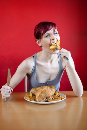 skinny woman: Skinny woman with a whole chicken on her plate stuffing herself with baked potatoes. Diet concept.