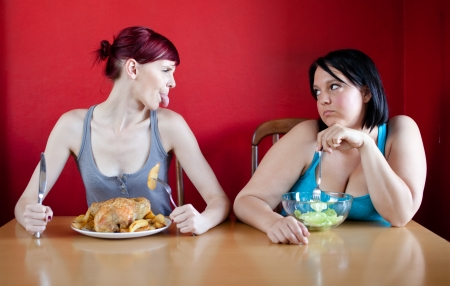 Skinny girl with a whole chicken teasing fat girl who's on a diet and eating salad photo