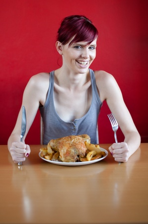 Happy skinny woman with a chicken on her plate. Diet concept. photo