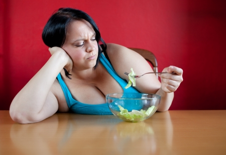 dieting: Unhappy overweight woman with her meal a bowl with a few leaves of lattuce in it. Diet concept.