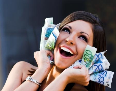 corporate greed: Beautiful joyful girl with Euro bills