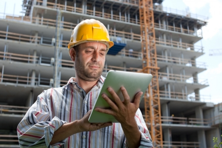 Construction specialist using a tablet computer. At a construction site.  photo