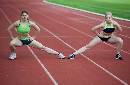 Couple of young female runners stretching on a running track photo