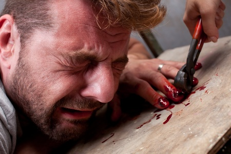 A man in agony, he's being denailed by a woman. Torture series. Stock Photo - 9830703